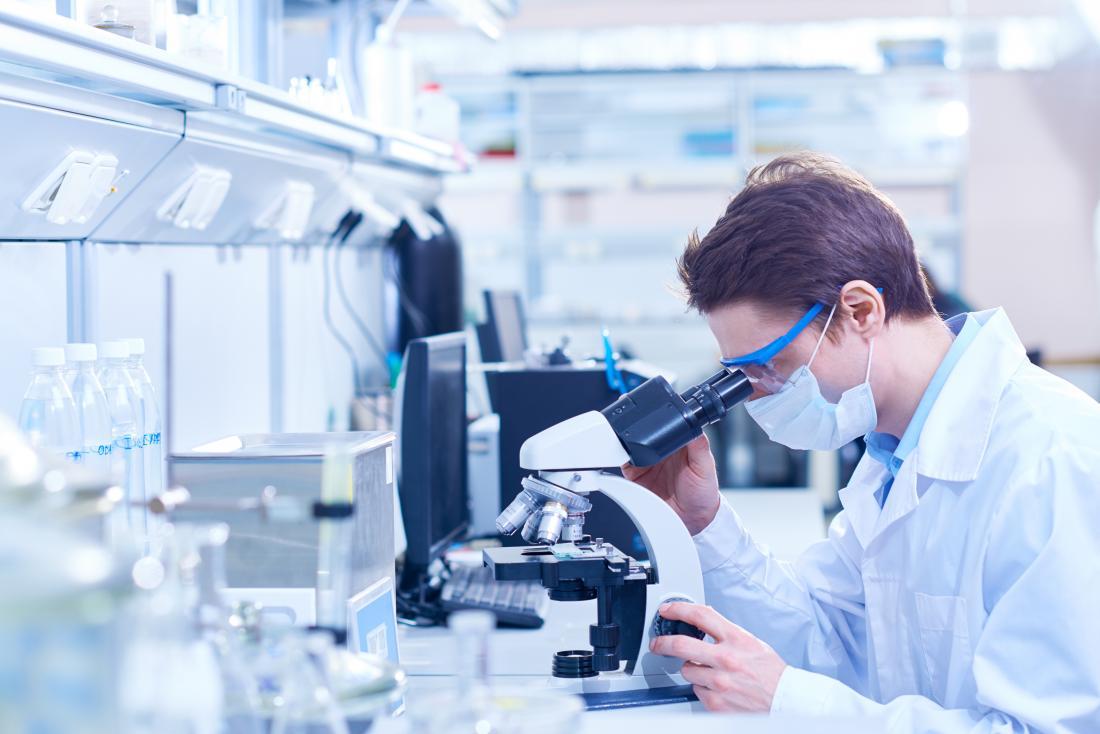 Lab technician looking through microscope
