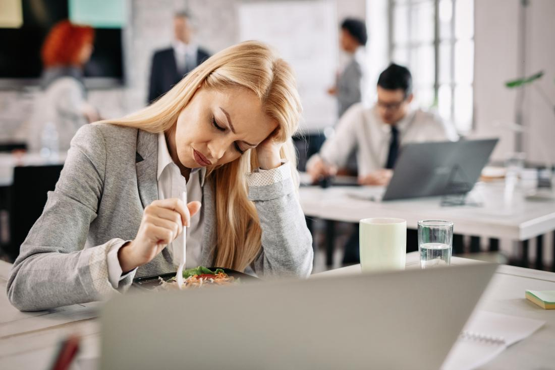 Woman struggling with food at her desk due to pregnancy