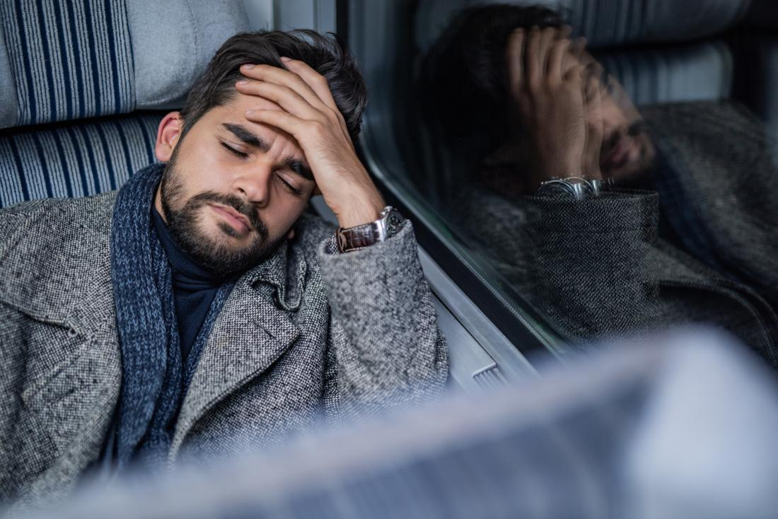 man with headache or migraine holds head leaning against the vehicle window