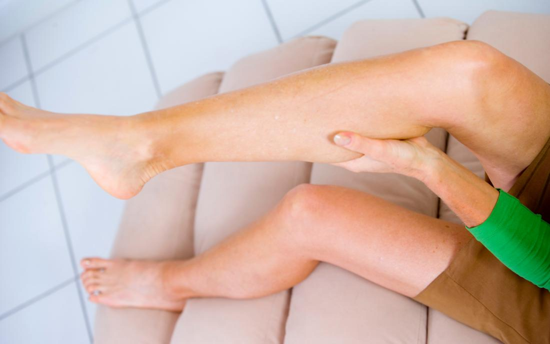 a woman holding her leg and wondering How to stop leg muscle cramps