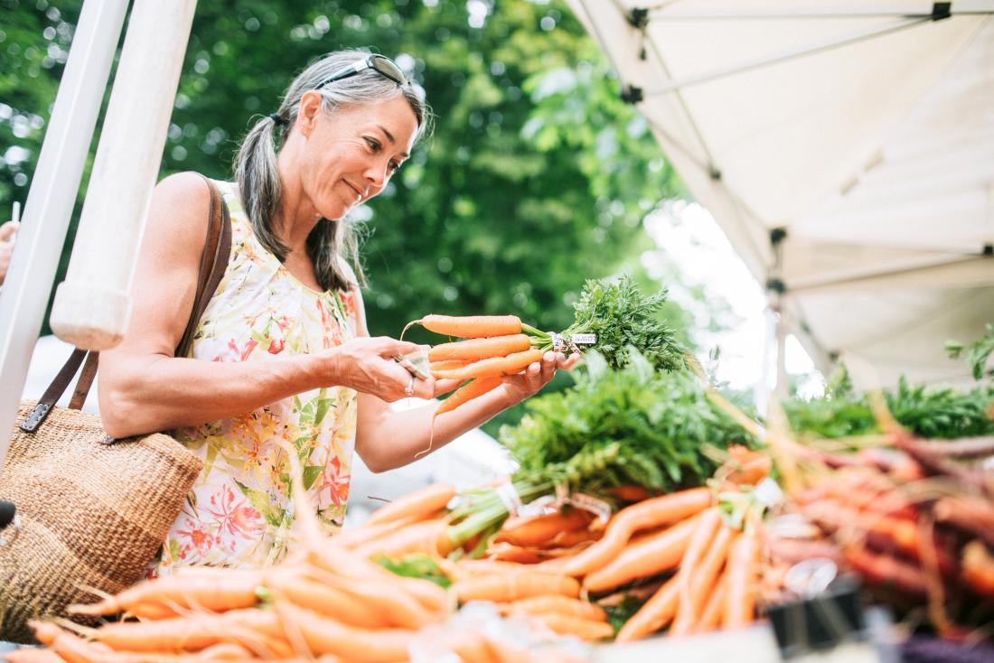 Woman holding carrots shopping for sustainable diet at outdoor farmers market.