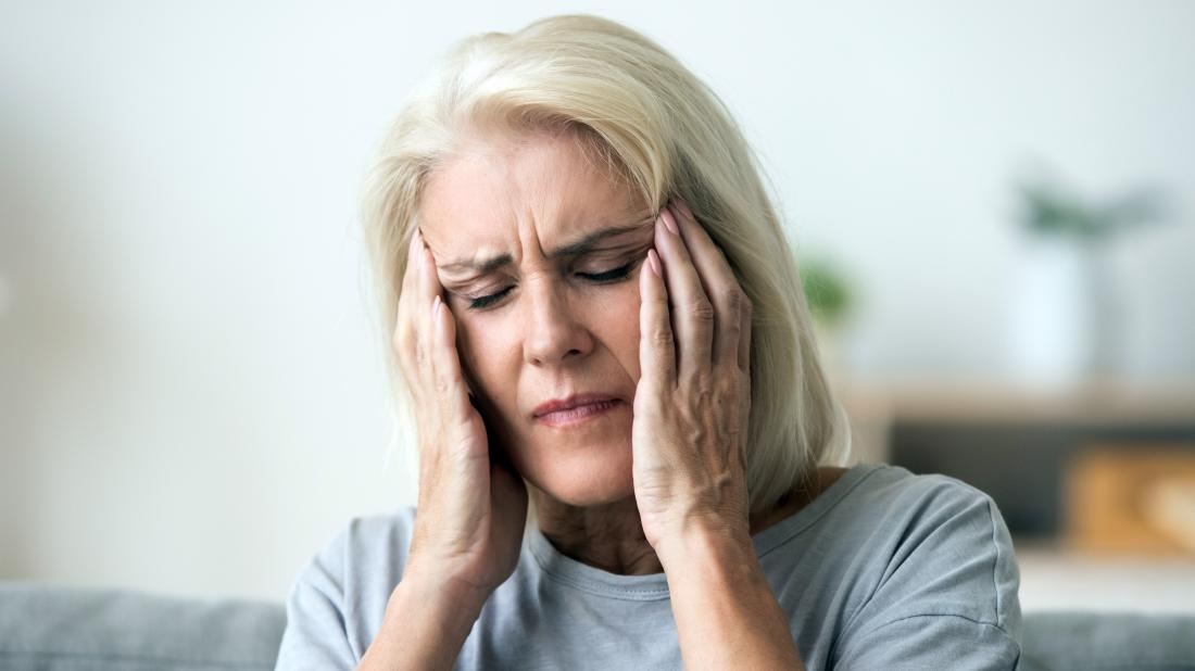 a women holding her temples because she is experiencing oscillopsia