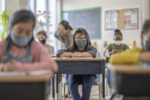 Group of elementary school classmates wearing protective face masks in the classroom while desks are socially distanced due to new COVID-19 regulations.