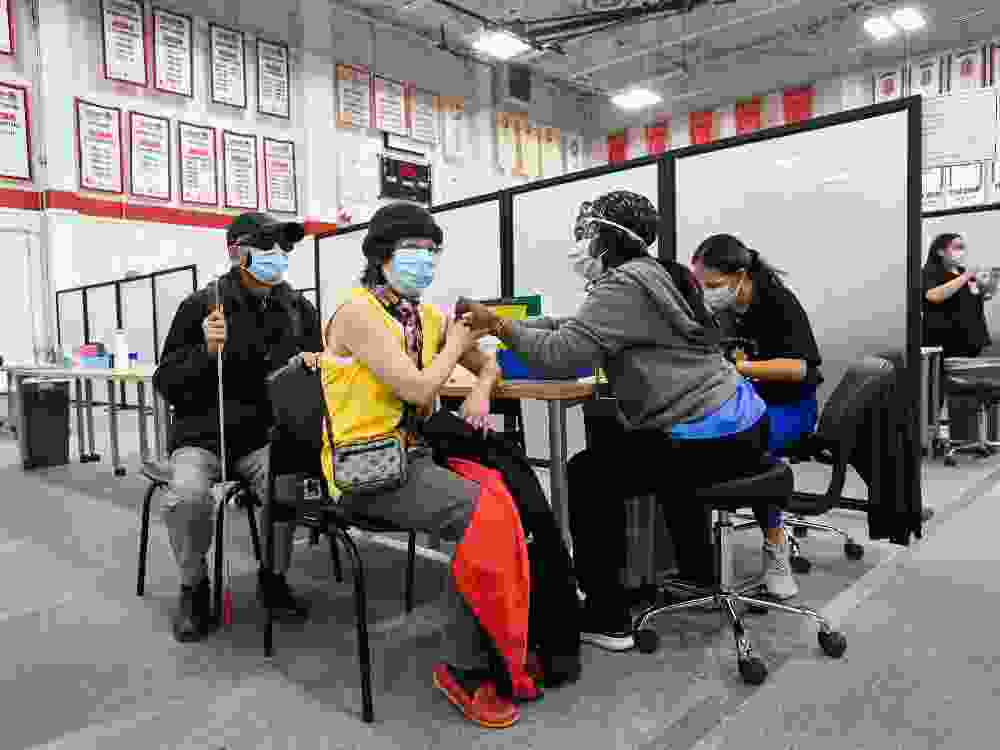 A woman receives her COVID-19 vaccine at the Seneca College mass vaccination site this spring.